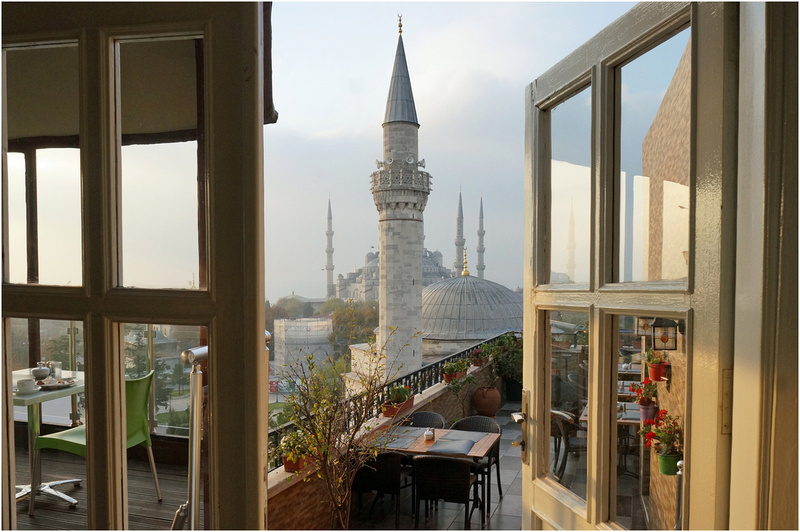 View at dawn of Sultan Ahmed Mosque from hotel terrace. Minaret and dome of Firuz Aga Mosque in foreground.